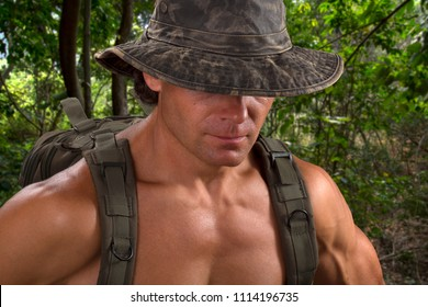 Closeup muscular shirtless adventure man wearing camo hat hiding eyes and backpack hiking in tropical jungle