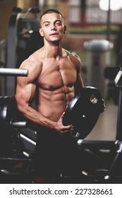 Closeup of a muscular young man lifting weights.
