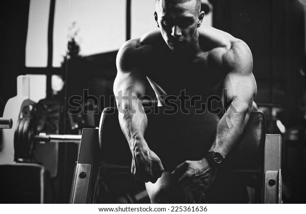 Closeup of a muscular young man lifting weights. Fine art. B&W
