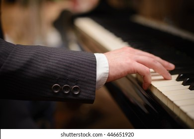 Close-up of a music performer's hand playing the piano