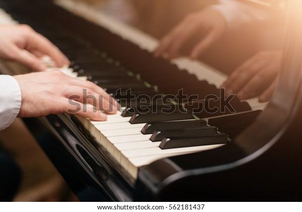 Nahaufnahme der Hand eines Musikdarstellers beim Klavierspielen