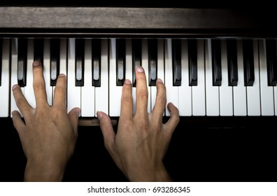 closeup musician hands playing piano on piano keyboard.low key tone image.concept for live music festival.Instrument on stage,classical music.abstract musical background.