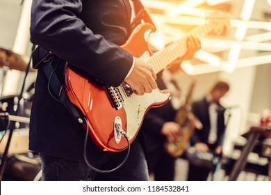 close-up musician lead electric red guitar in live concert musical band