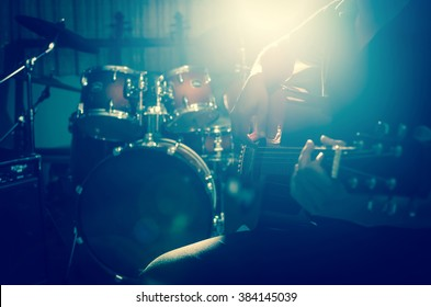 Closeup musician playing the guitar on band background with spot light,focus at finger of hand playing guitar, musical concept
