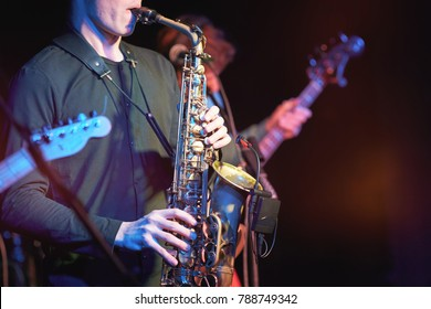 Closeup of musicians performing at a concert in a nightclub. Saxophonist and two guitarists.