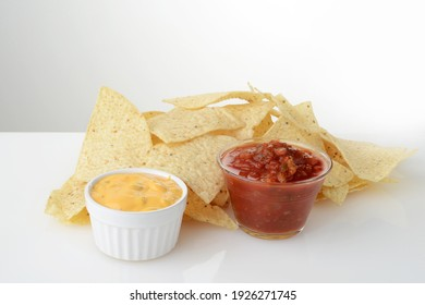 closeup nacho chips with bowls of salsa and cheese