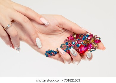 Closeup nail polished pastel multicolored long nails coral pink, white with crystals, hand holding perfume magenta blue green broach jewel isolated white background. Classic wedding bride nails design