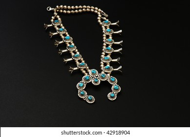 Closeup of  Native American Squash Blossom Necklace isolated on black background.  A beautiful, handcrafted piece of silver and turquoise jewelry.