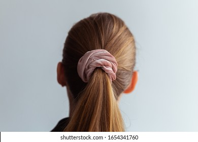 Close-up of a natural blonde hair, tied up in a ponytail by pink velvet scrunchie, back view