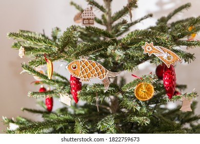 Close-up of natural Christmas tree decorated in retro style. Beautiful Xmas still life. Red decorations and traditional ornate baked gingerbreds or dry orange slices hanging on spruce branches detail.