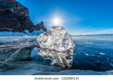 Close-up natural ice on frozen water in Lake Baikal with sunny blue sky, Siberia, Russia.