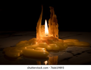 Closeup of a nearly burned down candle, lots of wax on the table
