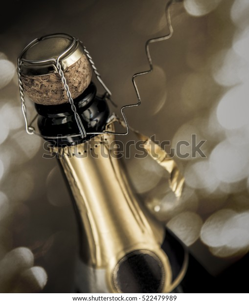 Close-up from nearly opened sparkling wine bottle with sparks on the background.