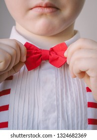 close-up neat little boy correcting his red bow tie. body parts hands and face child puts on scarlet bowtie. concept good breeding and education - Image
