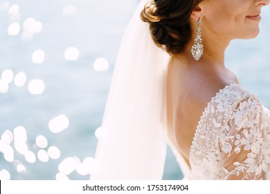 Close-up of the neck and neck of the bride, face profile. Beautiful big earring in ears, shoulder with white lace dress on background of glare of water. Fine-art wedding photo in Montenegro, Perast.