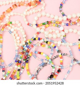 Closeup of necklaces made from multicolored beads and pearls on a pink pastel background.
