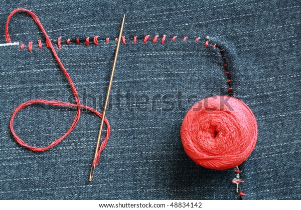 Closeup of needle and red thread on hole-ridden jeans textured