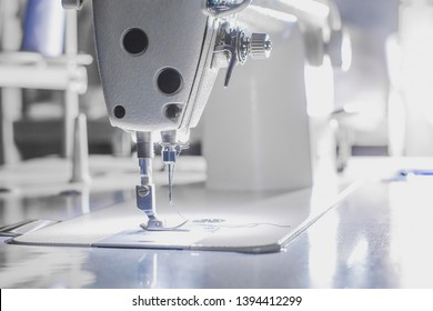 Close-up needle of white industrial sewing machine with white light.