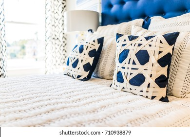 Closeup of new bed comforter with decorative pillows in bedroom in staging model home, house or apartment