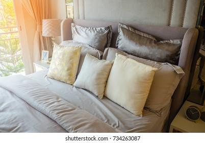 Closeup of new bed comforter with decorative pillows, headboard in bedroom in staging model home