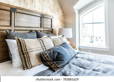 Closeup of new bed comforter with headboard, side table, lamp, decorative pillows in bedroom in staging model home, house or apartment by window with sunlight