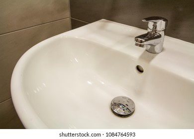 Close-up of new modern ceramic clean empty white washbasin sink connected to the sewer on background of nice light beige ceramic tiles. Professional plumbing and installation concept.