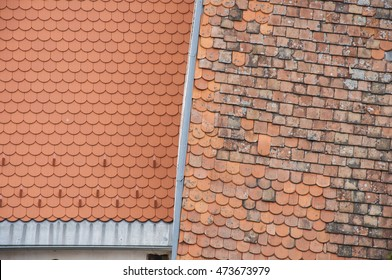 Closeup of new and old roof orange shingles with ridge tiles