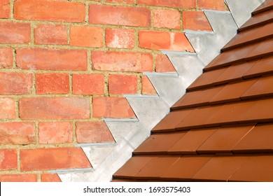 Cierre de las nuevas baldosas de arcilla rojiza y plomo que parpadea sobre un techo acristalado en el Reino Unido
