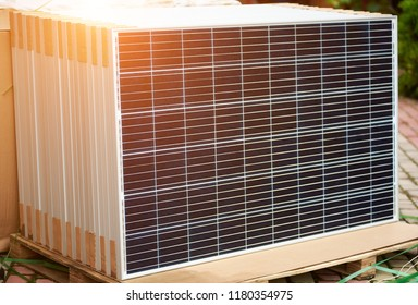 Close-up of new solar photo voltaic modules set outdoors ready for buying, transportation and installation. Renewable eco-friendly green energy production and environment preservation concept.