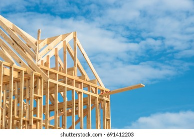 Closeup new stick built home under construction under blue sky in Humble, Texas, US. Framing structure/wood frame of wooden houses/home. House construction and real estate concept background. Panorama