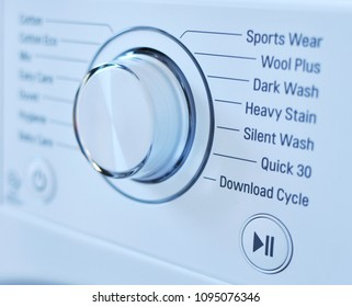 Closeup of new white laundry or washing machine cycle selector, with selective focus.