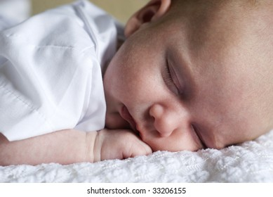 A closeup of a newborn baby boy sleeping, full frame with selective focus, horizontal