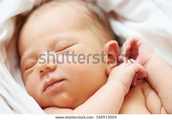 Close-up newborn baby sleeping in white bedsheet