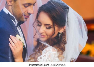 Close-up of newlyweds covered with a wedding veil embracing each other