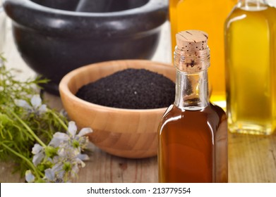 Close-up of nigella sativa oil in a bottle, against of nigella seeds and flowers on wooden background. Black cumin healing herb. Cold pressed, non refined oil. Traditional medicine.