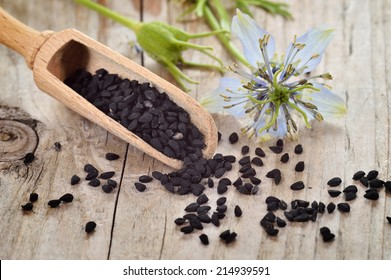 Close-up of nigella sativa seeds on wooden spoon and nigella flower on wooden table. Aromatic black cumin seeds.