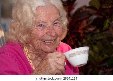 Closeup of a ninety year old woman smiling as she drinks from a teacup.