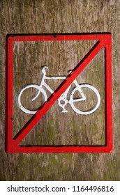 Close-up of a no cycling sign on a wooden post.