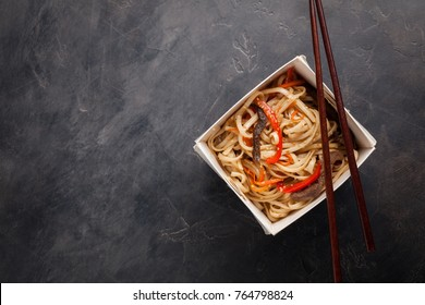 Close-up of noodles in a box with vegetables and beef in teriyaki sauce. Top view of Asian food, and wooden sticks. The concept of fast food. Copy space.