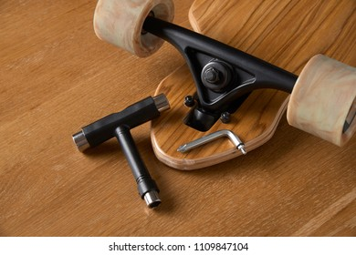 closeup of nose and truck of longboard and T tools for maintenance on a wooden background