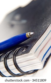 close-up of notebook and a blue pen