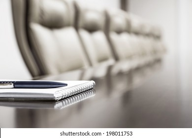 Closeup of notepad for agenda kept on table in empty corporate conference room before business meeting