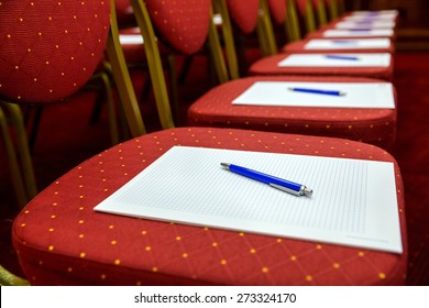 Closeup of notepad with pen for agenda on chairs in empty corporate conference room before business meeting