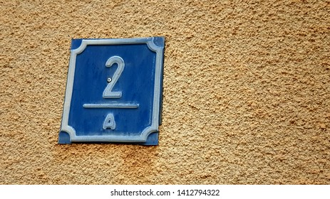 closeup of numeral two on house number 2A in blue and white painted sign on colourful sandy textured surface