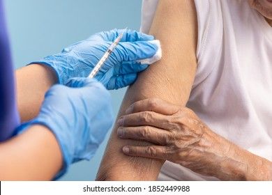 Closeup nurse doing vaccine injection to senior woman.