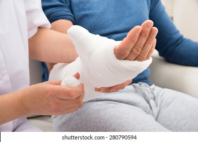 Close-up Of A Nurse Dressing Patient's Hand With Bandage