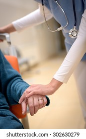 Close-up of nurse holding senior patient hand sitting in wheelchair