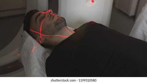 Close-up. Nurse pushing buttons on mri tomograph. Man lays in Magnetic Resonance Image device, making tomographic scanning. The laser shines on the face of the patient.