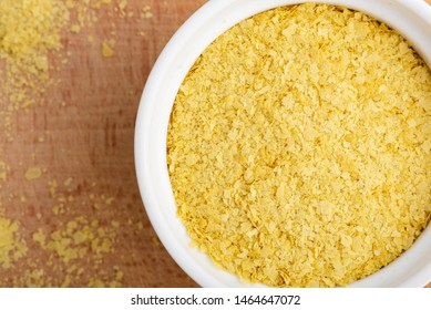 Closeup of nutritional yeast flakes in a bowl, top view