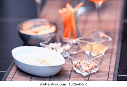 Closeup of nuts and glasses with cocktails with  straws.